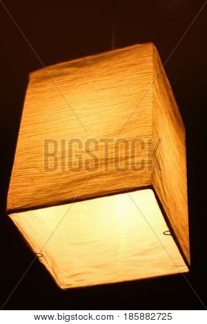 Textile lamp shape of a parallelepiped shines a warm yellow light at night
