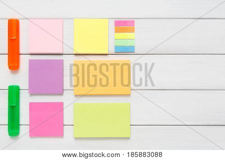 Flat lay of office stationery supplies - colorful markers, sticky notes and memo blocks, notepad on white rustic wood background, top view with copy space, nobody, objects