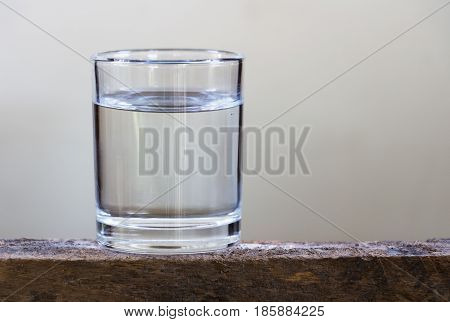 Drink a glass of water on a wooden floor.