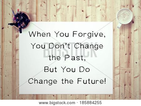 Inspiring motivation quote handwritten on a notepad when you forgive, you don't change the past, but you do change the future. White pad paper image.