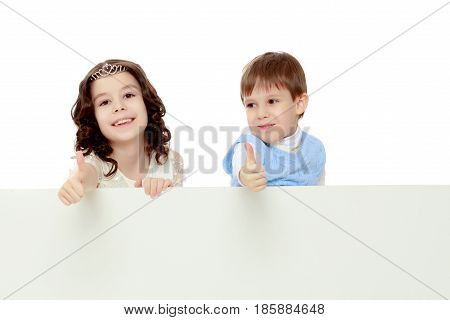 A boy and a girl peeping from behind the white banner. Children show a gesture all okay. Isolated on white background.