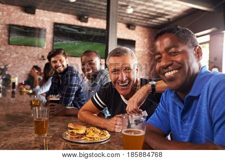 Portrait Of Male Friends At Counter In Sports Bar