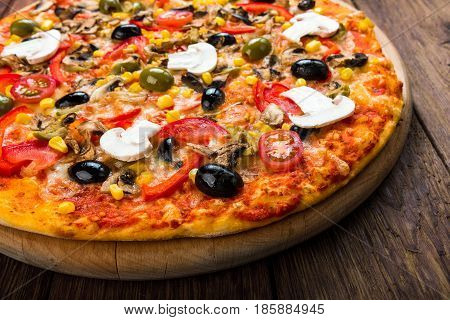 Italian pizza closeup with ham, tomatoes and black olives - thin pastry crust at wooden table background