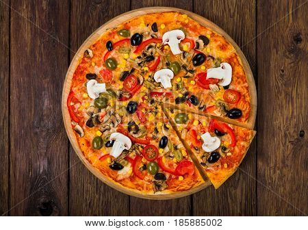 Italian pizza top view on wood with ham, tomatoes and black olives - thin pastry crust