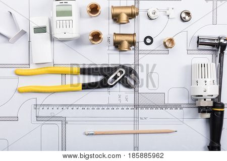 Elevated View Of A Thermostat And Work Tools On Blueprints