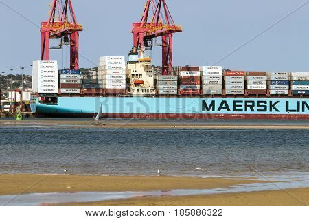 Low Tide And Container Vessel And Loading Cranes
