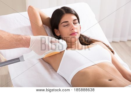 Young Woman Having Underarm Laser Hair Removal Treatment In Beauty Spa Clinic
