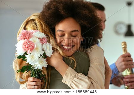 Shot of a woman hugging a friend and holding flowers.