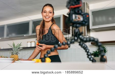 Young Woman Recording Content For Her Blog In Kitchen.