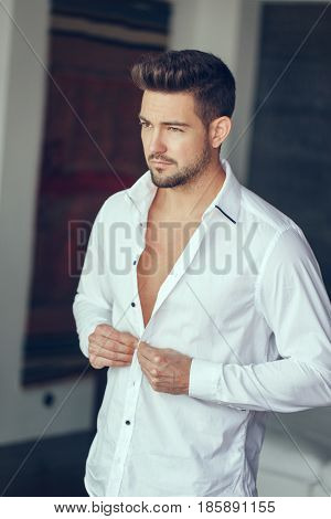 Young rich confident man buttoning shirt indoor