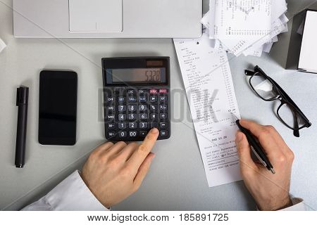 Elevated View Of A Businessperson Calculating Bill Using Calculator On Office Desk