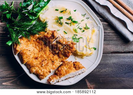 Homemade Sliced Wiener Chicken Schnitzel with herb and mashed potatoes on plate on wooden table background. Healthy food.