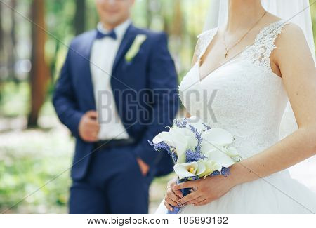bride in white dress with wedding bouquet of white Callas in the background the groom in a blue suit