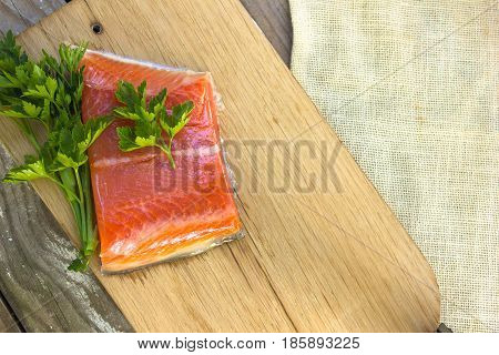 Fresh salted salmon fillet with parsley and onion on a wooden board. Concept of healthy food