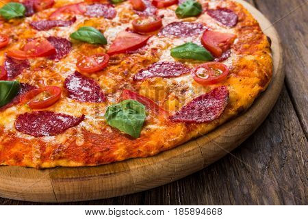 Italian pizza closeup with salami pepperoni - thin pastry crust at wooden table background