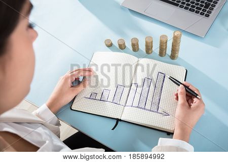 Close-up Of A Businessperson Drawing Graph On Note Book With Coin Stacks Over The Desk