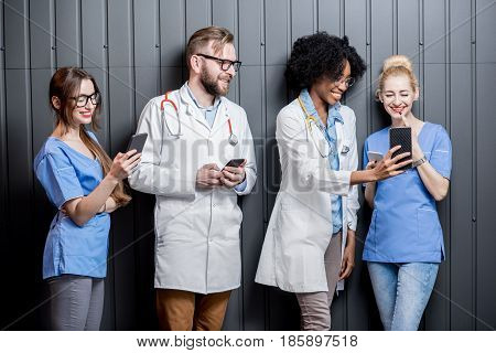 Multi ethnic group of medics having fun standing with phones on the gray wall background