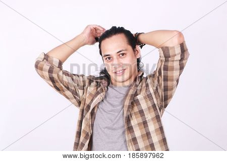 Photo image portrait of a cute young Asian male model smiling while tying his long hair