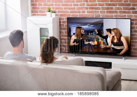 Rear View Of Couple Sitting On Couch Watching Television At Home