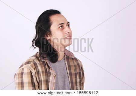 Photo image portrait of a cute young Asian male student with long hair smiling looking up and thinking
