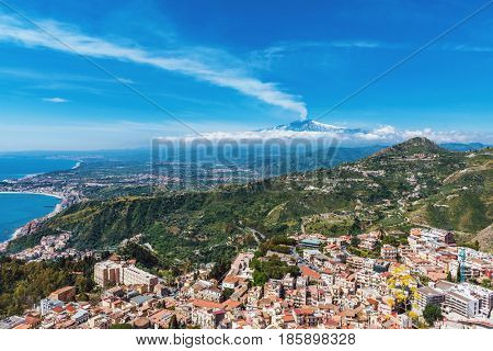 Aerial cityscape view of Taormina, located on a hillside with Etna volcano in the background, Sicily, Italy