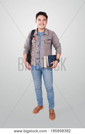 Photo image portrait of a cute young Asian male student standing looking at camera and smiling while holding some books full body portrait