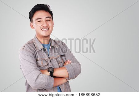 Photo image portrait of a cute young successful Asian male student smiling and standing with arms crossed in front of his chest