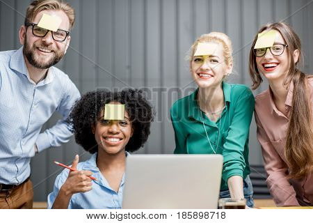 Coworkers with stickers on the face working with laptop together at the office