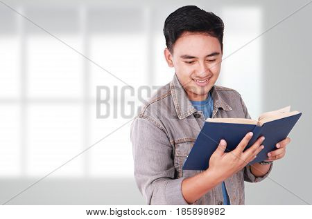 Photo image portrait of a cute young Asian male student standing and smiling while reading a book