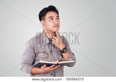 Photo image portrait of a cute young Asian male student standing looking up and thinking while reading a book