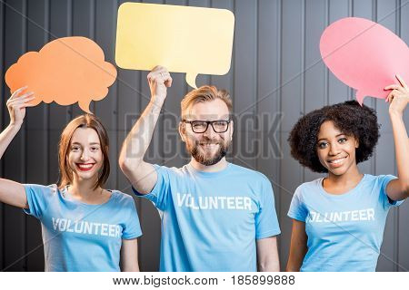 Volunteers holding colorful thought bubbles standing on the gray wall background