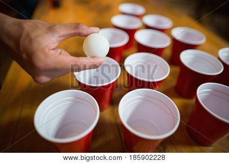 Cropped hand of man playing beer pong in bar