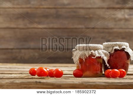 the fresh tomatoes and tomato sauce on wooden background