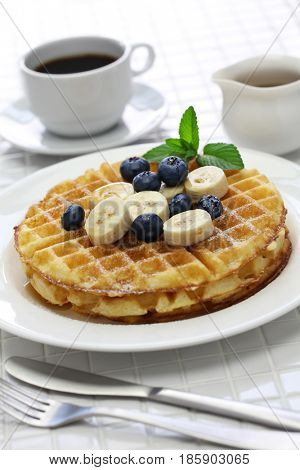 homemade american round waffles with blueberry and banana pouring maple syrup