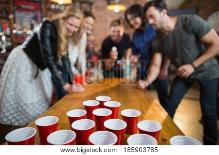 Friends enjoying beer pong game on table in bar
