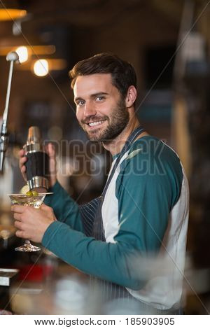 Portrait of bartender making drinks in bar