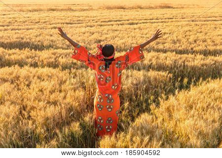 African woman in traditional clothes standing arms raised in a field of barley or wheat crops at sunset or sunrise