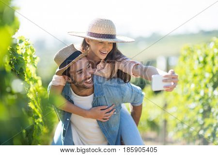 Happy couple taking selfie while piggybacking at vineyard during sunny day