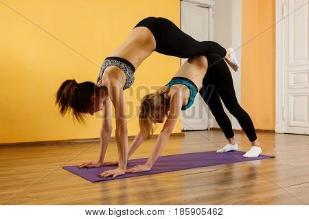 Photography of two sportswomen practicing yoga in gym