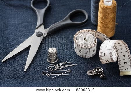Scissors Thimble Pins Centimeter Tape Thread Button On Black Jeans Fabric Close Up And Top View.