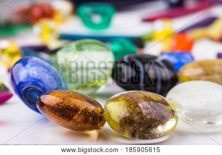 Handmade glass beads mix closeup. Selective focus.