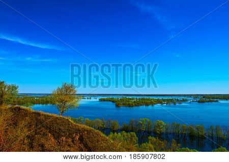 Beautiful spring landscape. Amazing view of the floods from the hill. Europe. Ukraine. Impressive blue sky with white clouds