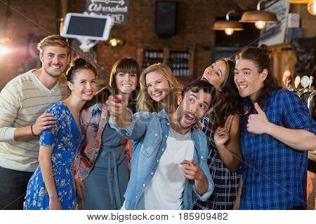 Cheerful friends taking selfie through mobile phone in pub