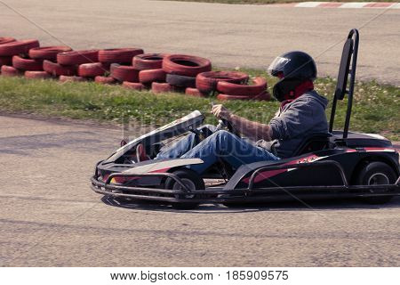 man drive go kart on track side view outdoor shot