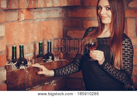 Woman Tasting Wine In Rural Cottage Interior