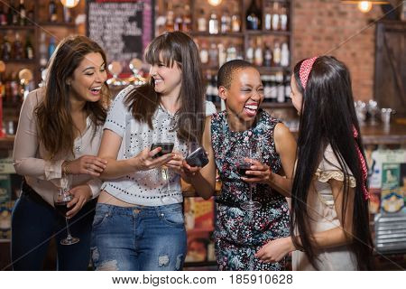 Cheerful woman using mobile phone at pub