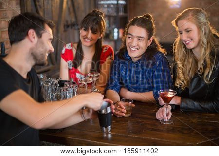 Smiling friends looking at bartender making drinks for them in pub