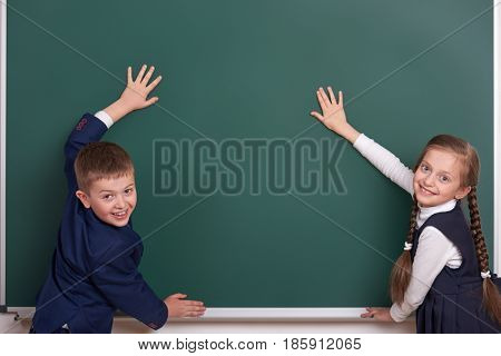 elementary school boy and girl put hands on chalkboard background and show blank space, dressed in classic black suit, group pupil, education concept