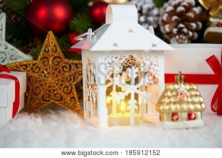 christmas decoration on white fur with fir tree branch closeup, gifts, xmas ball, cone and other object on dark background with lights, winter holiday concept