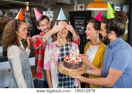 Happy friends with cake giving suprise to woman during her birthday